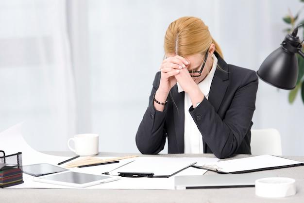 Empresaria joven frustrada en el lugar de trabajo con el papel; tableta digital; ordenador portátil en el escritorio