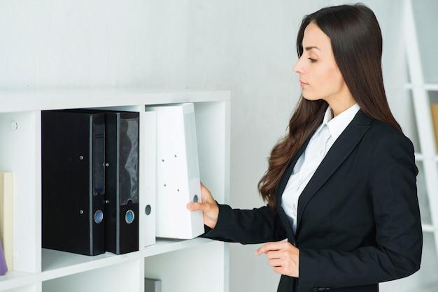 Empresaria joven hermosa que quita la carpeta blanca del estante en la oficina