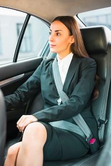 Empresaria joven hermosa que se sienta dentro del coche
