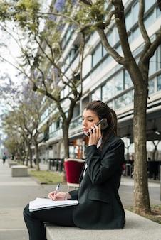 Empresaria joven ocupada que se sienta fuera del edificio que habla en la escritura del teléfono móvil en carpeta con la pluma
