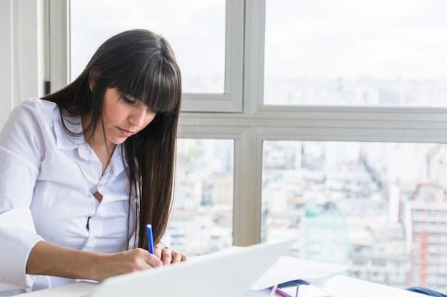 Empresaria joven con el ordenador portátil en el escritorio que trabaja en la oficina