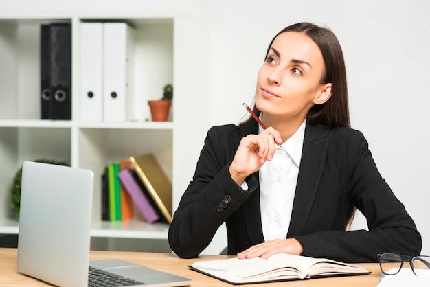 Empresaria joven pensativa con el diario y el ordenador portátil en el escritorio de madera en la oficina