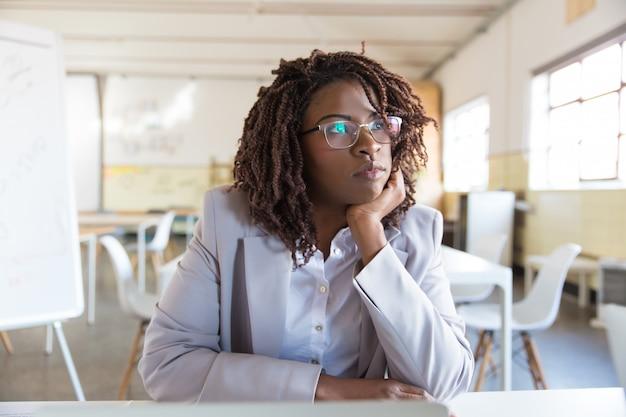Empresaria joven pensativa que se sienta en oficina