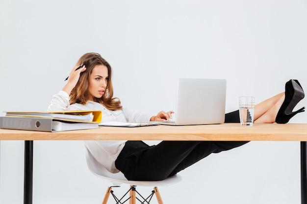 Empresaria joven pensativa usando la computadora portátil y pensando con las piernas sobre la mesa sobre fondo blanco.
