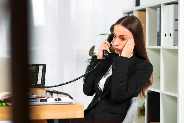 Empresaria joven preocupada que se sienta cerca del escritorio de madera que escucha en el teléfono