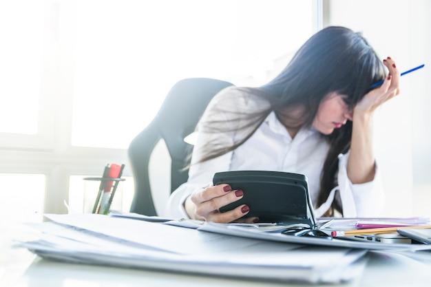 Empresaria joven preocupada que sostiene la calculadora sobre el escritorio del trabajo