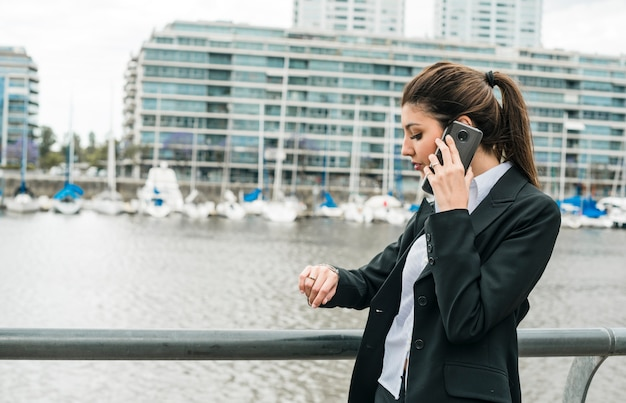 Empresaria joven que se coloca cerca del puerto que controla el tiempo