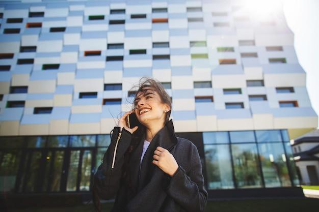Empresaria joven que habla en el teléfono móvil durante descanso para tomar café al aire libre, cerca del edificio de oficinas.