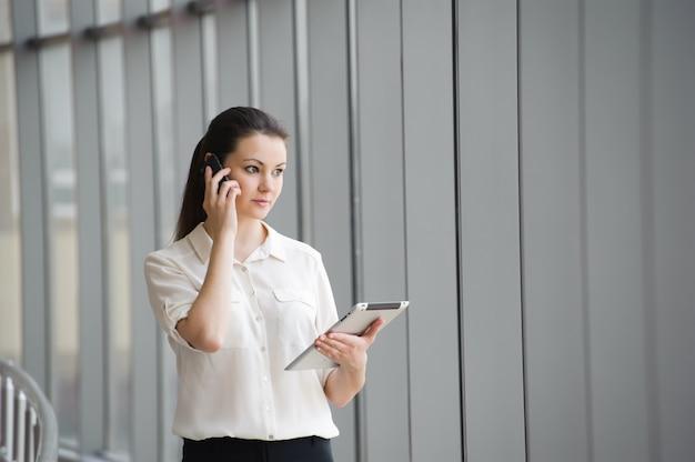 Empresaria joven que habla en el teléfono móvil mientras que hace una pausa la ventana en oficina. hermosa joven modelo femenino en una oficina brillante.