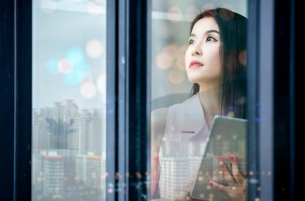 Empresaria joven que hace una pausa la ventana mientras que sostiene la tableta y mira afuera.