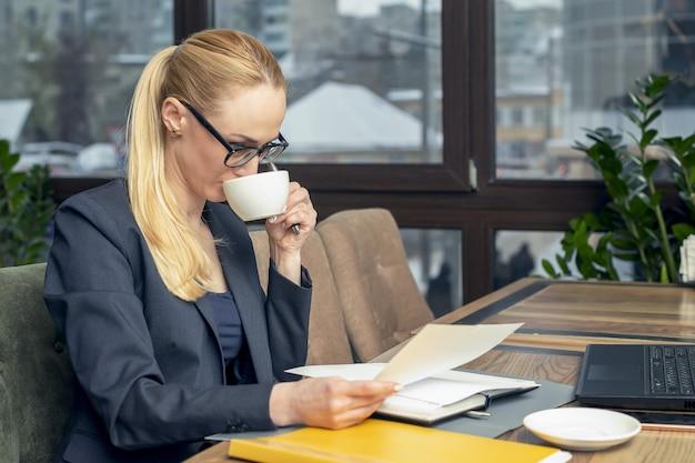 La empresaria joven que lleva los vidrios que se sientan en cafetería en la mesa lee documentos delante del ordenador portátil y bebe café.