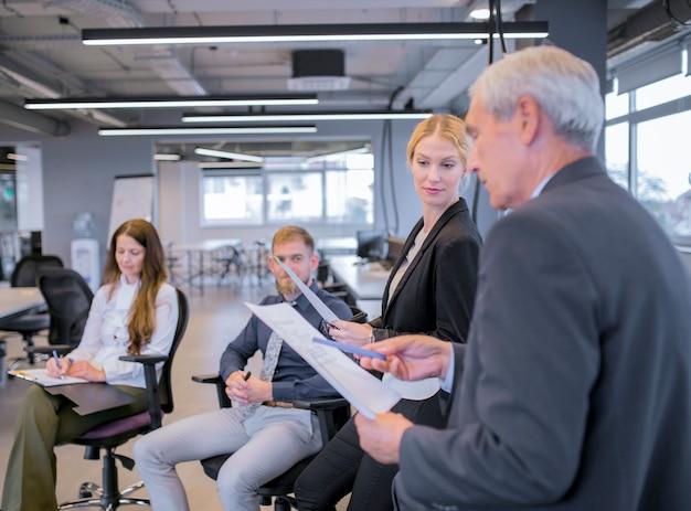 Empresaria joven que mira al hombre de negocios mayor que señala documentos en su mano