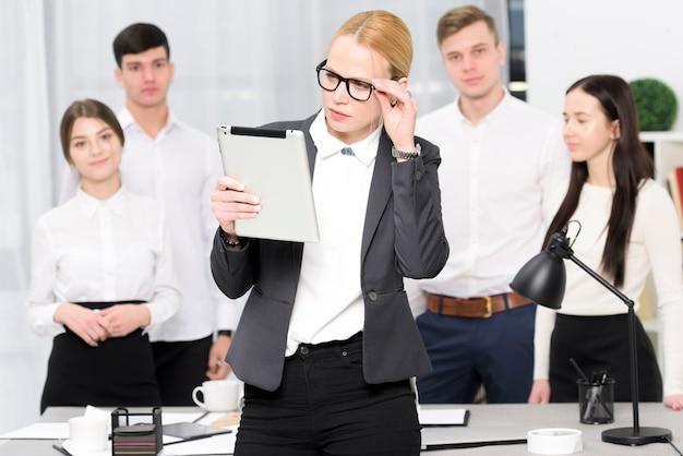 Empresaria joven que mira la tableta digital que se coloca delante de hombres de negocios en oficina