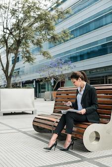 Empresaria joven que se sienta fuera del edificio que mira el teléfono móvil