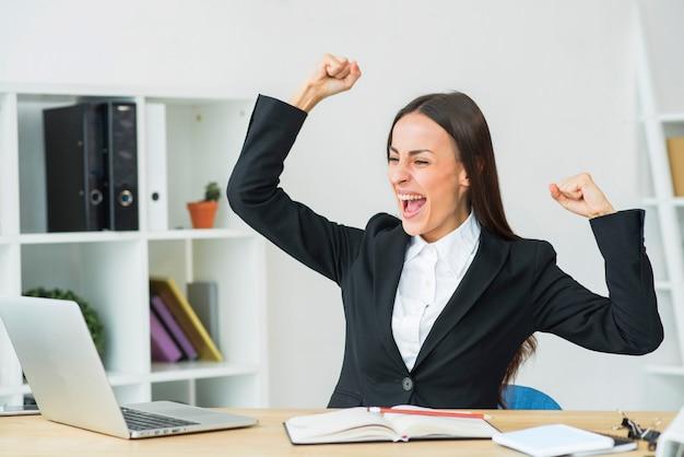 Empresaria joven que se sienta en la oficina que aprieta su puño con alegría
