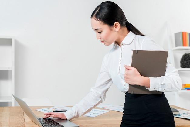Empresaria joven que sostiene el diario a disposición usando el ordenador portátil en la tabla en el lugar de trabajo