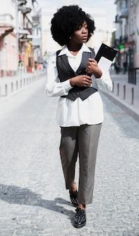 Empresaria joven que sostiene el tablero y la tableta digital disponibles que caminan en el camino