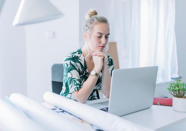Empresaria joven que trabaja en la computadora portátil en oficina
