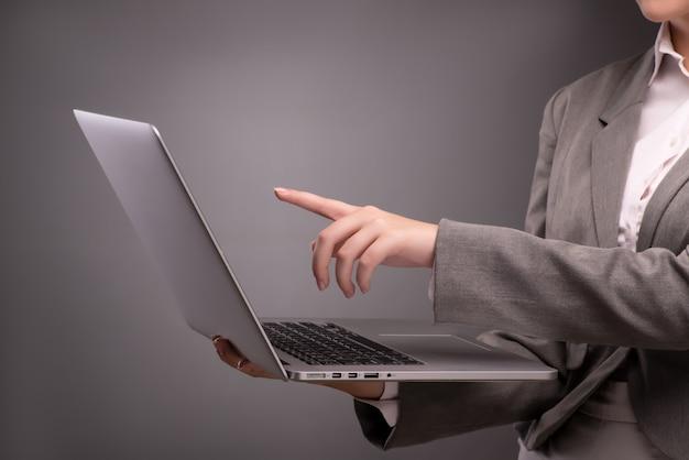 Empresaria joven que trabaja con el ordenador portátil en concepto del negocio