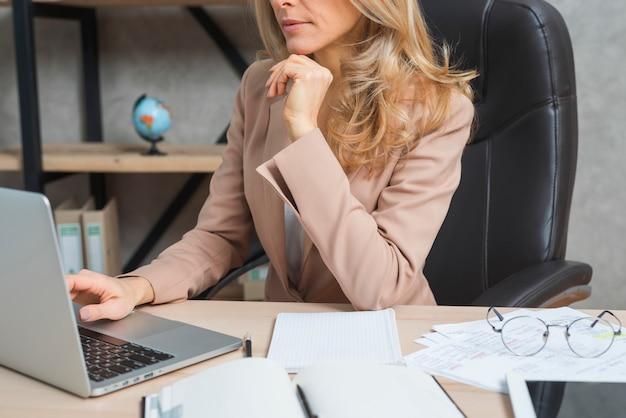 Empresaria joven que usa el ordenador portátil con el diario y documentos en el lugar de trabajo