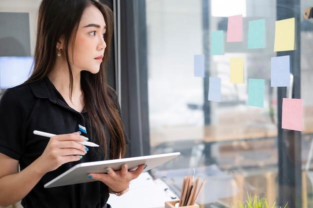 Empresaria joven que usa la tableta que busca la comercialización de la información en línea.