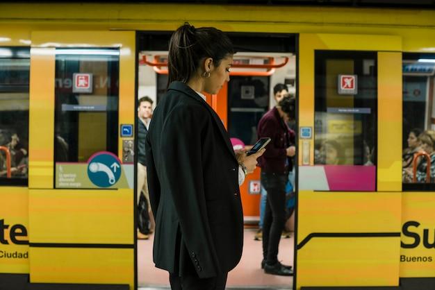 Empresaria joven que usa el teléfono móvil que se coloca delante del tren subterráneo