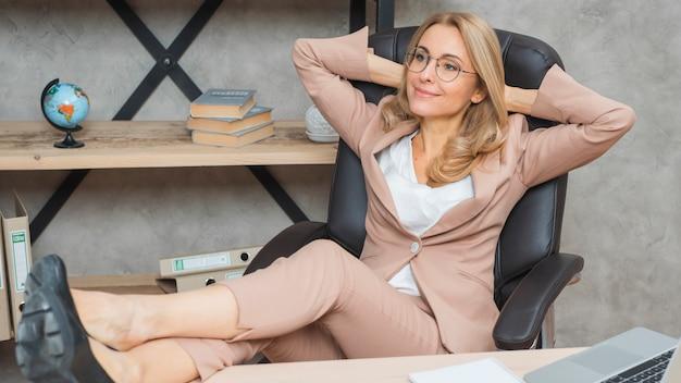Empresaria joven relajada que se sienta en silla con las piernas cruzadas en la tabla en la oficina