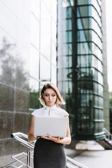 Empresaria joven rubia que se coloca delante del edificio de oficinas usando el ordenador portátil