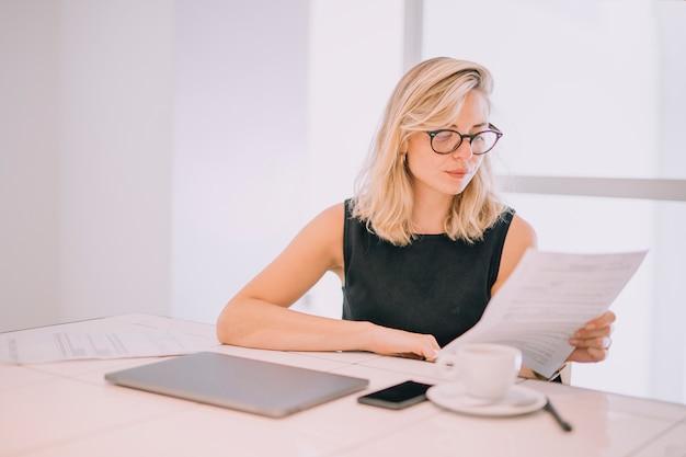 Empresaria joven rubia que lee el documento en el lugar de trabajo con la taza de café; portátil y celular en mesa