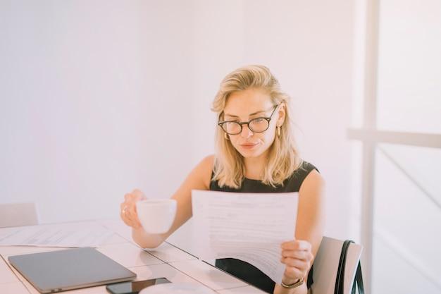 Empresaria joven rubia que sostiene la taza de café que lee el documento en el lugar de trabajo