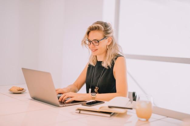 Empresaria joven rubia sonriente que usa el ordenador portátil con el desayuno en la tabla de la oficina
