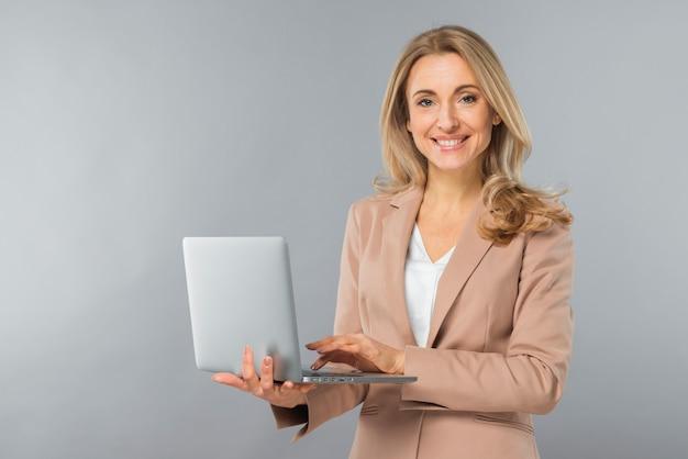 Empresaria joven rubia sonriente que usa el ordenador portátil a disposición contra el contexto gris