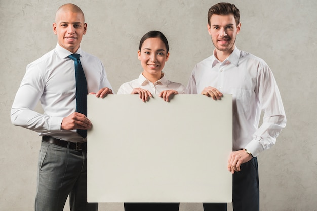 Empresaria joven sonriente confiada con sus dos colegas que llevan a cabo el cartel en blanco