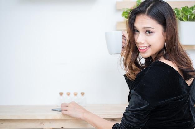 Empresaria joven sonriente hermosa que usa la tableta digital en café