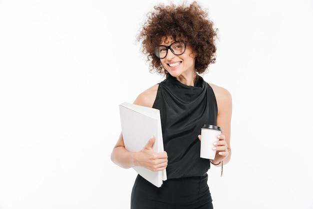 Empresaria joven sonriente en las lentes que sostienen la computadora portátil