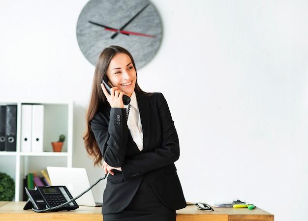 Empresaria joven sonriente ocupada en hablar en el teléfono en la oficina