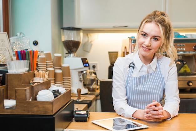 Empresaria joven sonriente que se coloca en la cafetería con la tableta digital