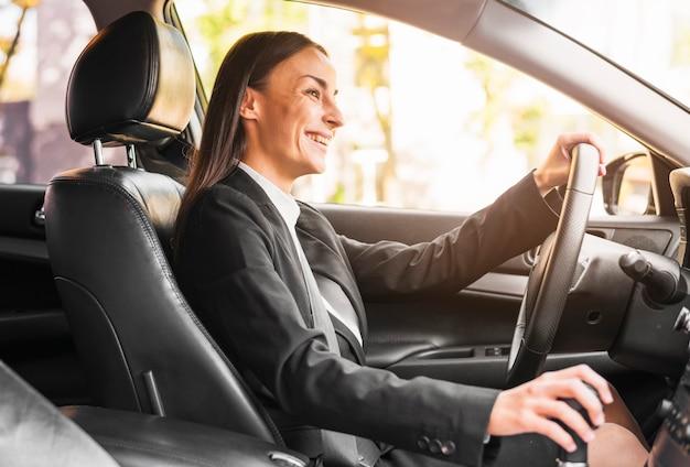 Empresaria joven sonriente que conduce un coche