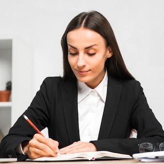 Empresaria joven sonriente que escribe notas del diario con el lápiz