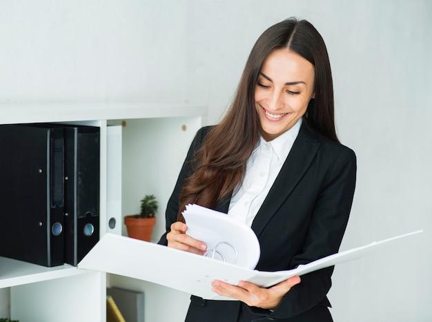 Empresaria joven sonriente que mira los documentos en la carpeta de la pizca