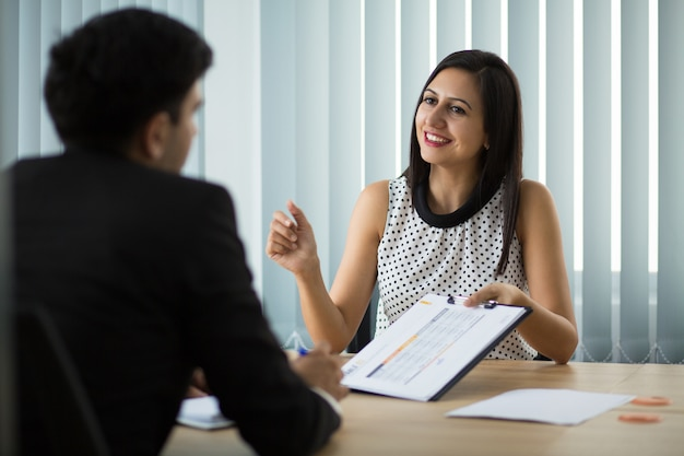 Empresaria joven sonriente que muestra el contrato al socio