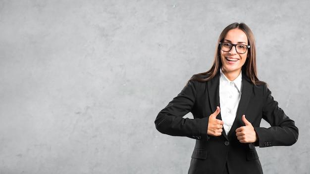 Empresaria joven sonriente que muestra el pulgar encima de la muestra contra el contexto gris