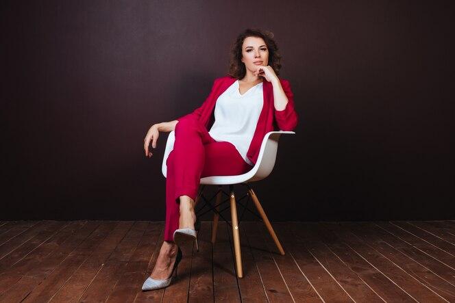Empresaria joven sonriente que se sienta en la silla de la oficina sobre fondo oscuro