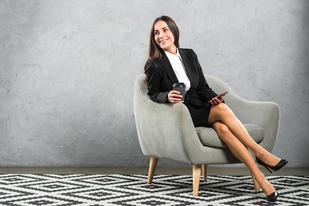 Empresaria joven sonriente que se sienta en la butaca que sostiene la taza y el teléfono móvil de café disponibles