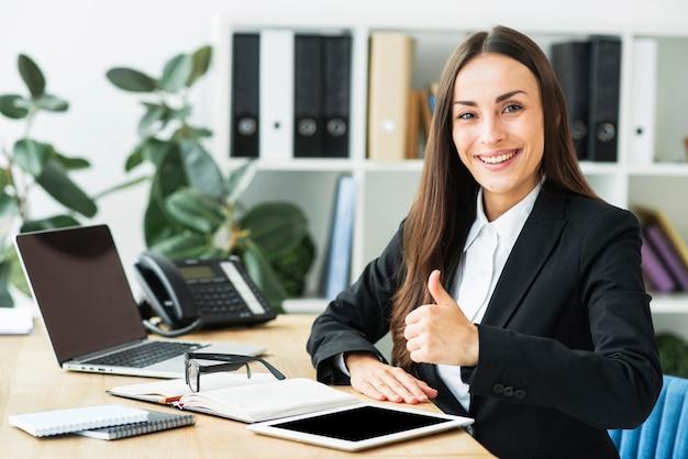 Empresaria joven sonriente que se sienta en el lugar de trabajo que muestra el pulgar encima de la muestra