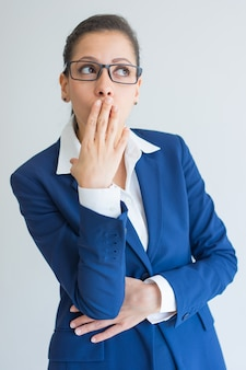 Empresaria joven sorprendida que cubre la boca con la mano.