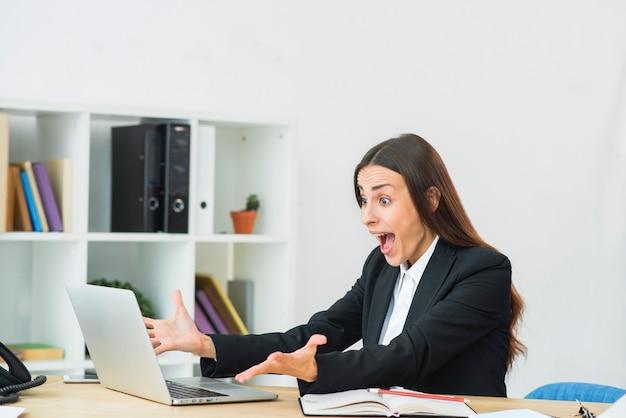 Empresaria joven sorprendida que mira la computadora portátil