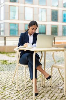 Empresaria con laptop y papeles en café