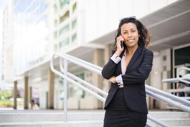 Empresaria latinoamericana hablando por teléfono sonriendo. ella está al aire libre. espacio para texto.