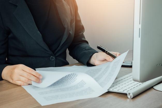Empresaria leyendo y comprobando el documento de términos y condiciones en su escritorio